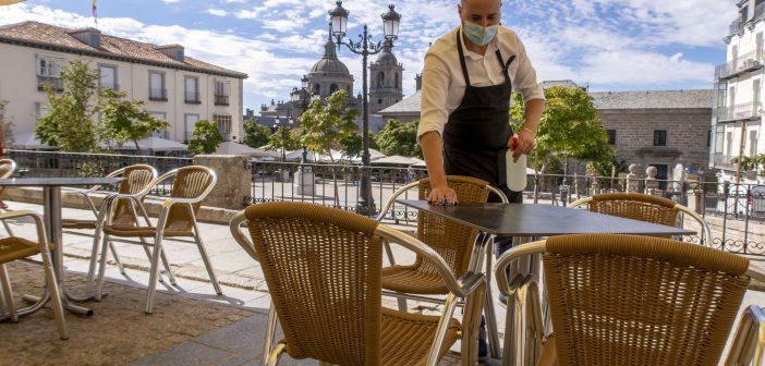Camarero desinfectando una mesa de la terraza